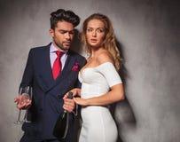 Взгляд со стороны элегантной пары с шампанским и стеклами стоковое фото rf