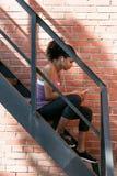 Взгляд со стороны sporty женщины сидя на лестнице Стоковые Изображения RF