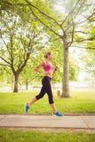Взгляд со стороны sporty женщины jogging в парке Стоковое фото RF