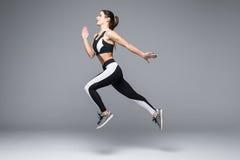 Взгляд со стороны sporty скакать молодой женщины изолированный на серой предпосылке стоковое фото