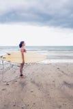 Взгляд со стороны surfboard нося женщины на пляже Стоковые Фото