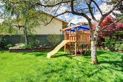 Взгляд спортивной площадки детей в зеленом саде задворк с деревьями березы Стоковое Изображение