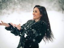 Взгляд счастливой девушки брюнет играя с снегом в ландшафте зимы Красивая молодая женщина на предпосылке зимы Привлекательная жен Стоковая Фотография
