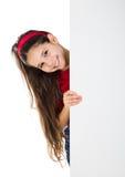 Взгляд украдкой девушки вне от вертикального белого знамени Стоковые Изображения