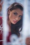 Взгляд украдкой женщины вне от заднего белого занавеса около окна Стоковые Изображения RF