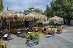 Взгляд уютного nook для релаксации лета под навесом ладони с баром, таблицей, стулом и деревянной скамьей, gradina Borisova парка Стоковое Изображение RF