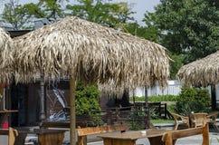 Взгляд уютного nook для релаксации лета под навесом ладони с таблицей, стулом и деревянной скамьей, gradina Borisova парка Стоковая Фотография RF