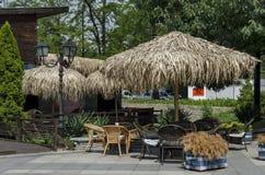 Взгляд уютного nook для релаксации лета под навесом ладони с таблицей, стулом и деревянной скамьей, gradina Borisova парка Стоковые Изображения RF
