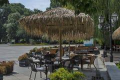 Взгляд уютного nook для релаксации лета под навесом ладони с таблицей, стулом и деревянной скамьей, gradina Borisova парка Стоковое Фото