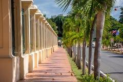 Взгляд улицы в Санто Доминго, Доминиканской Республике, с винтажной стеной на левой стороне и деревьями на правильной позиции Стоковое фото RF