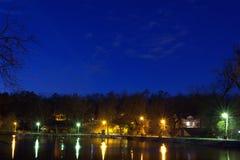 Взгляд улицы парка ночи с озером и деревьями 2 Стоковые Фото