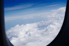 Взгляд через иллюминатор на голубом небе в облаках Стоковые Изображения