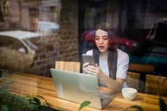 Взгляд через окно очаровательной девушки с сотовым телефоном в руках думает что написать в текстовом сообщении для ее парня, пока Стоковое Изображение