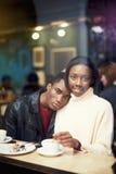 Взгляд через окно очаровательной молодой женщины сидя в кафе при ее парень, темнота снял кожу с пар наслаждаясь и липкой жидкость Стоковая Фотография RF