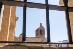 Взгляд через окно с ржавой решеткой в церковь с колоколами Стоковое фото RF