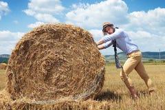 Взгляды вскользь человека напольные на вас и стоге сена нажимов Стоковая Фотография RF