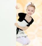 Взгляды украдкой девушки вне от заднего белого знамени Стоковое Изображение RF