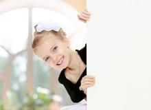 Взгляды украдкой девушки вне от заднего белого знамени Стоковая Фотография
