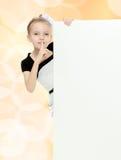 Взгляды украдкой девушки вне от заднего белого знамени Стоковые Фото