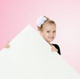 Взгляды украдкой девушки вне от заднего белого знамени Стоковое Фото