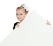 Взгляды украдкой девушки вне от заднего белого знамени Стоковые Изображения RF