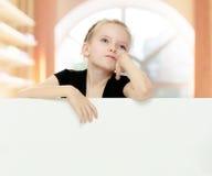Взгляды украдкой девушки вне от заднего белого знамени Стоковые Фотографии RF