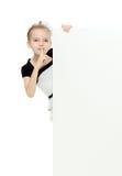 Взгляды украдкой девушки вне от заднего белого знамени Стоковые Изображения