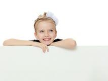 Взгляды украдкой девушки вне от заднего белого знамени Стоковое Изображение