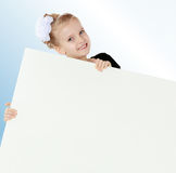 Взгляды украдкой девушки вне от заднего белого знамени Стоковое фото RF
