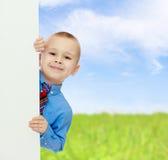 Взгляды украдкой мальчика вне от за знамени Стоковое фото RF