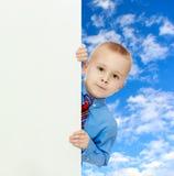 Взгляды украдкой мальчика вне от за знамени Стоковое Изображение RF