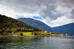 Взгляды фьордов, малой деревни, леса и гор в clou Стоковое Изображение