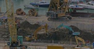 Взгляд экскаваторов выкапывая отверстие около дока фарфор Hong Kong сток-видео