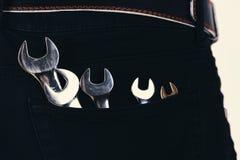 Взламывайте инструменты в джинсах pocket на белой предпосылке Оборудование гаечного ключа изготовленное металла Костюм Repairer и Стоковая Фотография RF