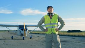 Взлетно-посадочная дорожка с пилотным положением около самолета и наушников извлекать 4K видеоматериал
