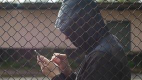 Взломщик хакера взбирается в телефоне в тюрьме за решеткой, конец-вверх, арест, компьютерная технология, рубя сток-видео