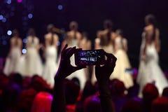 Взлётно-посадочная дорожка модного парада фотографируя с телефоном Стоковое Изображение RF