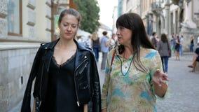 Взрослая дочь и красивая мать идут вдоль улицы города и обсуждают что-то горяче Красиво одетый акции видеоматериалы
