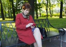 Взрослая женщина в красном пальто сидя на стенде в парке с пэ-аш Стоковое Изображение RF