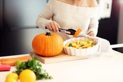 Взрослая женщина в кухне подготавливая блюда тыквы на хеллоуин Стоковые Фотографии RF