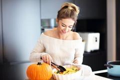 Взрослая женщина в кухне подготавливая блюда тыквы на хеллоуин Стоковые Фото