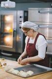 Взрослая женщина в стеклах печет торты в хлебопекарне стоковое изображение