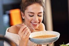 Взрослая женщина есть суп тыквы в кухне Стоковое Изображение RF