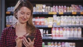 Взрослая женщина покупая качественные продучты в гипермаркете и использовании видеоматериал