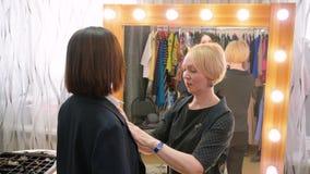 Взрослая женщина судя за новый портной пальто совместно в зеркале магазина модной одежды переднем Элегантная женщина выбирая паль сток-видео