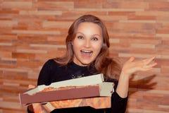 Взрослая женщина с коробкой пиццы выглядя счастливой стоковое изображение rf