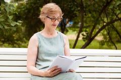 Взрослая женщина читает книгу в парке стоковое изображение