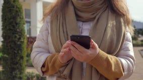 Взрослая женщина swiping над outdoors на улице города, концом-вверх экрана смартфона видеоматериал