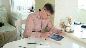 Взрослая краска человека с покрашенными красками акварели в домашней студии