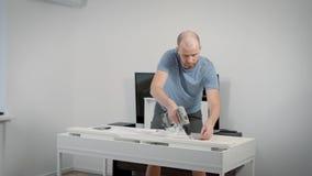 Взрослая отделка человека собирая его таблицу работы в доме сток-видео